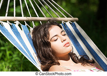 Young woman sleeping in a hammock in garden