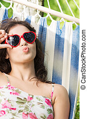 Young woman lying in a hammock in garden with heart shaped...