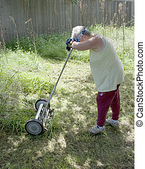Woman resting from mowing yard - A woman trying to mow high...