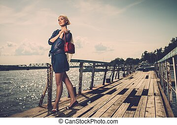 Stylish beautiful blond woman with white scarf and red bag...