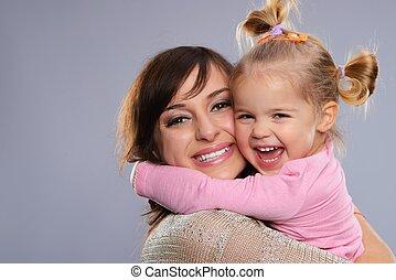 feliz, sonriente, joven, madre, abrazos, ella, poco, hija