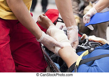 first aid training - Paramedic applying bandage to arm of an...