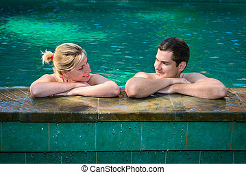 Happy smiling couple in swimming pool - Happy smiling couple...