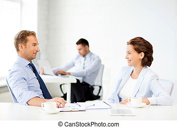 man and woman discussing something in office - smiling...