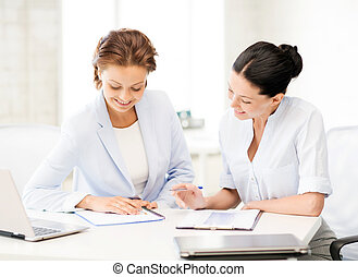 two smiling businesswomen working in office - picture of two...
