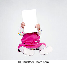 Blank space - Little baby girl holding blank paper over her...