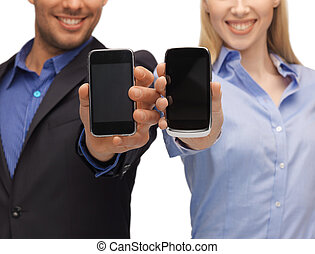 woman and man hands with smartphones - close up of woman and...