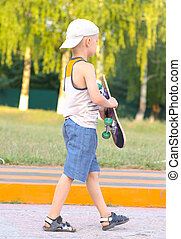 Boy Child going with Skateboard behind view Outdoor Summer...