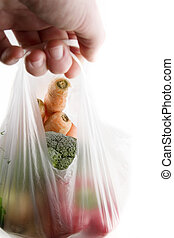 Vegetable Groceries - A clear plastic grocery bag filled...