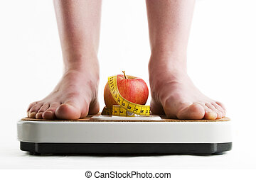 Diet - A pair of female feet standing on a bathroom scale...