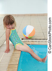 little girl in the water pool with a ball