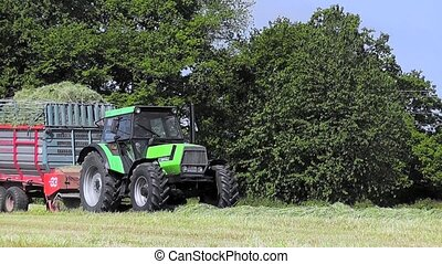 Farmer harvesting grass silage - Farmer driving a modern...