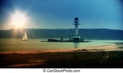 Lighthouse and boat sailing at sunset