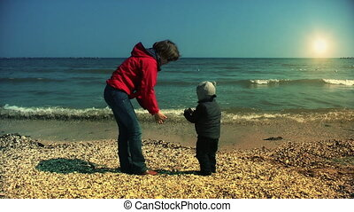 Mother and son throwing sea shells in water
