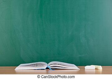 Open book on desk in front of a blackboard