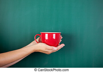 Coffee break - Hands holding a red cup against blackboard