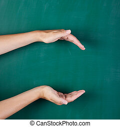 empty womans hands cupped against green board - Closeup of...