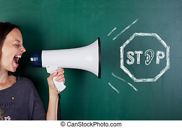 Closeup of woman shouting though megaphone with stop sign drawn on blackboard