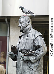 Statue Busker - A masked man, acting like a statue with a...