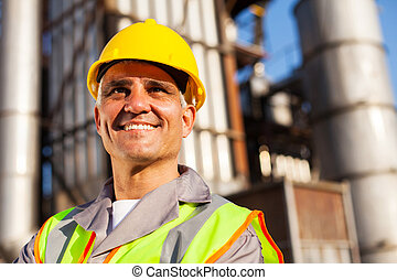 senior fuel refinery worker closeup portrait inside plant