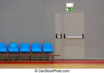 Exit Door - Emergency exit door next to a row of blue sits...