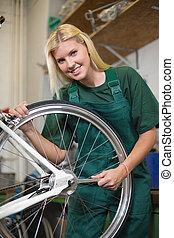 Female mechanic in workshop repairing a bicycle wheel