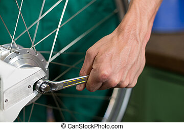Closeup of bicycle mechanic with a wrench repairing bike...