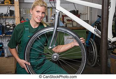 Bicycle mechanic repairing wheel on bike in a workshop