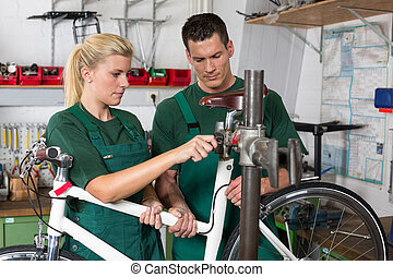 Bicycle mechanic and apprentice repairing a bike in workshop