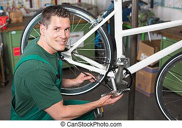 Bicycle mechanic repairing tooth belt in a workshop