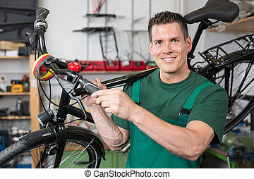 Bicycle mechanic carrying a bike in workshop