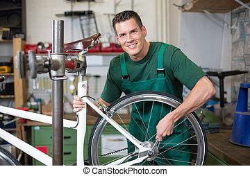 Mechanic repairing wheel on a bicycle in workshop