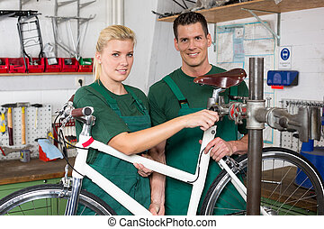 Bicycle mechanic and apprentice repairing a bike