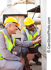 petrochemical technicians inspecting fuel tank - two...