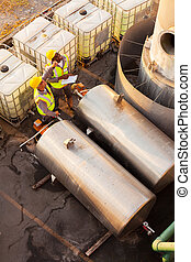 petrochemical co-workers working in plant - two...