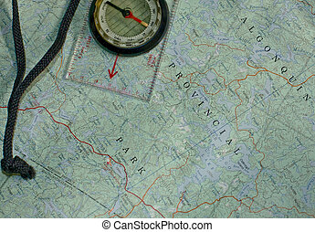 Topographical Map with Compass - A compass laying over a...