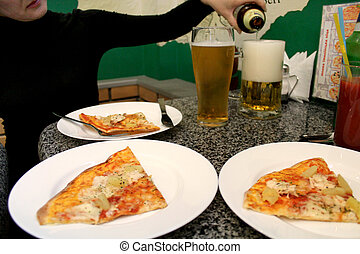 woman' s hand pouring beer in a glass and pizza - image of...