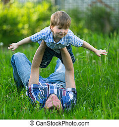 Father playing in the grass with his small son
