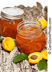 Apricot jam on wooden background