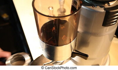 Bartender grinds beans in coffee mill, close-up