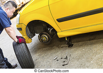 Changing Car Tire - A mechanic looking troubled is preparing...