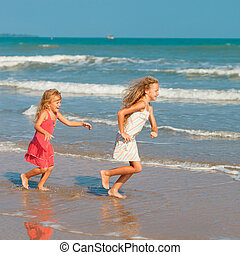 Happy kids playing at the beach
