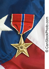 Bronze star on USA flag - Bronze star, awarded for valor in...