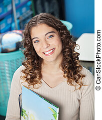 Teacher With Book In Kindergarten - Portrait of young female...