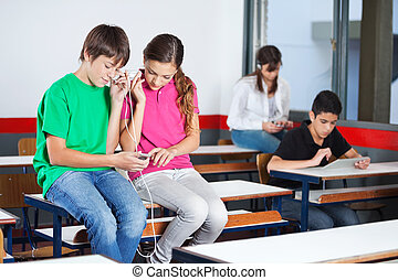 Teenage Schoolchildren Listening Music In Classroom -...
