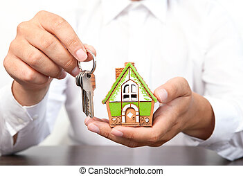 businessman holding a small house and apartment keys in hand...