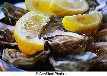 Oysters with lemon - Image of fresh oysters with lemon close...