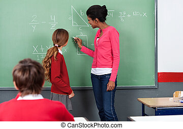 Teacher Teaching Mathematics To Students On Board - Young...