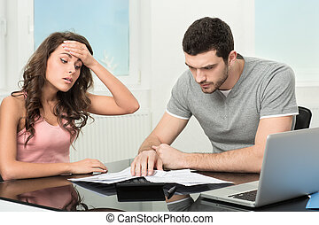 man upset after looking at card statement - Couple, Man...