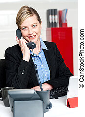 Pretty front desk lady attending clients call - Smiling help...